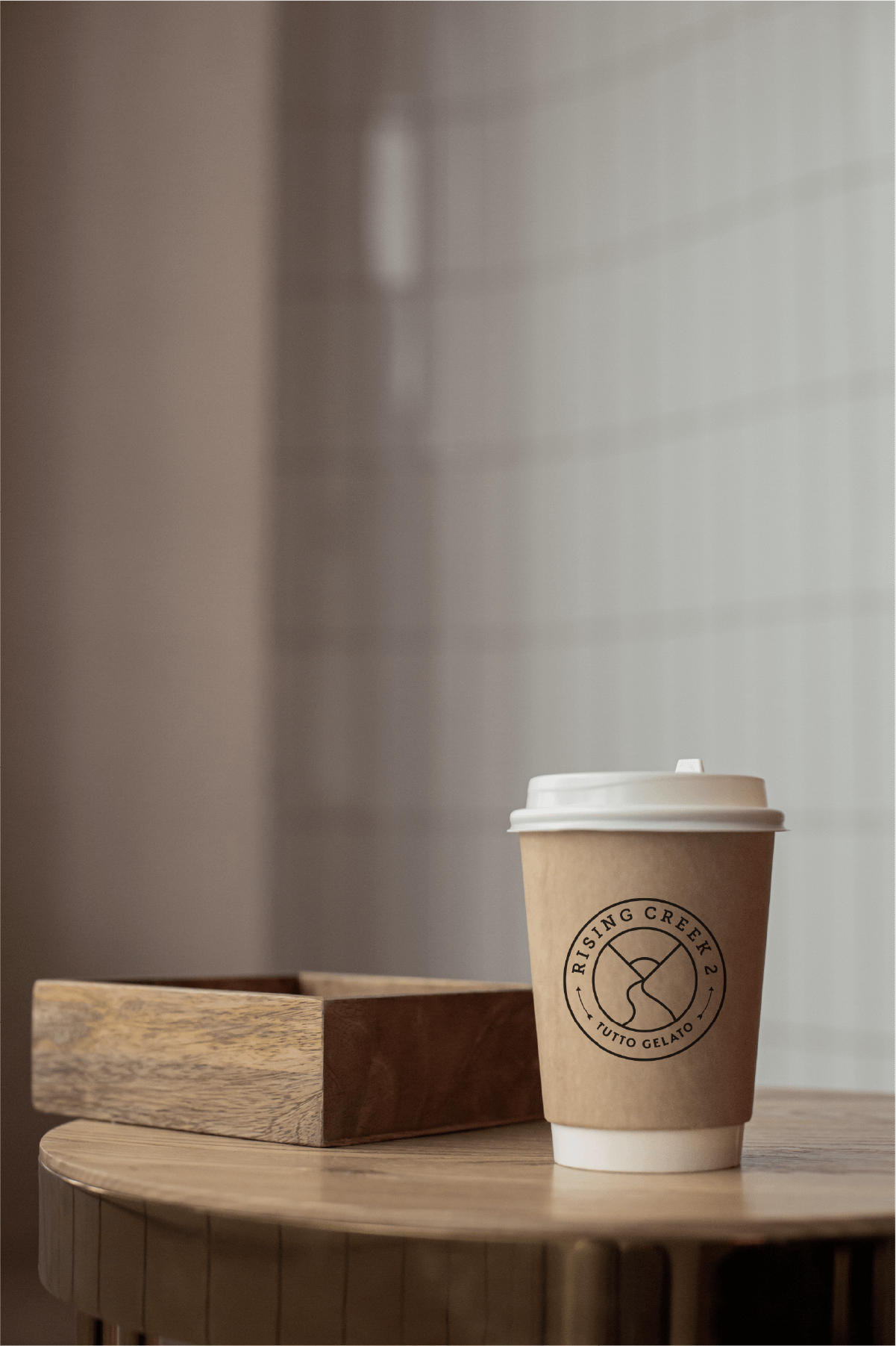 Carry-out coffee cup with the Rising Creek 2 logo printed on it