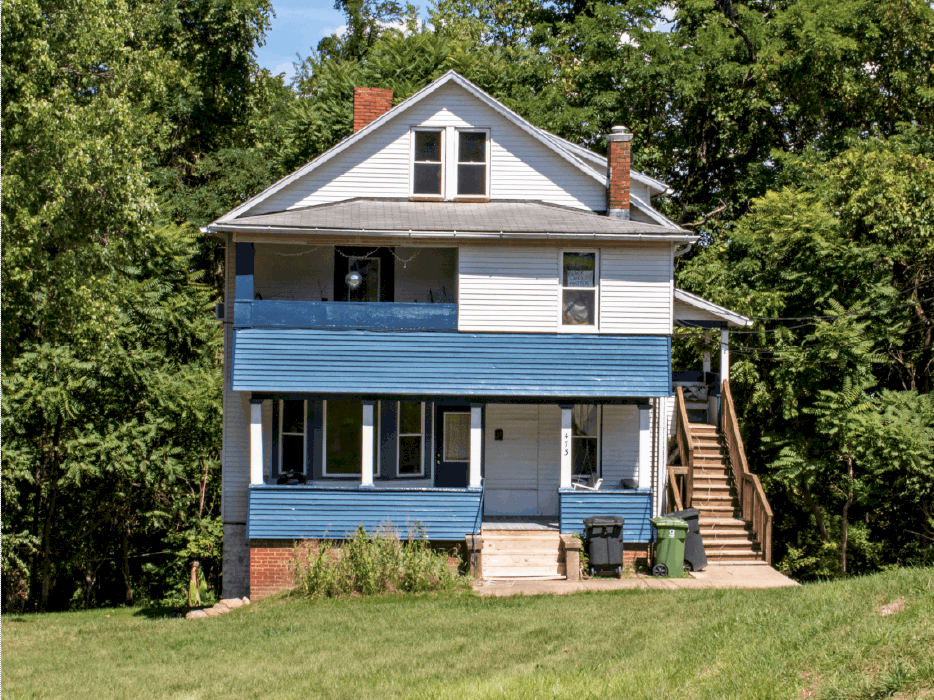 House with blue covered porch and large lawn